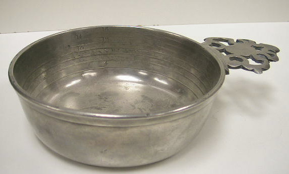 Mint condition pewter bleeding bowl.  Designed to measure the amount of b lood removed from patients.  These bowls can be differentiated from standard pewter porringers by the graduated rings and ounce markings.