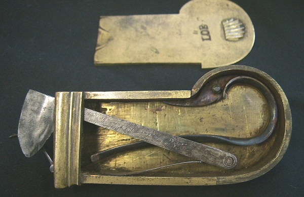 Very unusual brass cased Veterinary spring lancet.  Note that the blade retracts back behind the driver spring after firing.  The piece is decorated with a nice shell on the end of the release mechanism and on the back plate.  It is marked wiht the makers mark LOB.  Probably German in origin c.1800-1825.