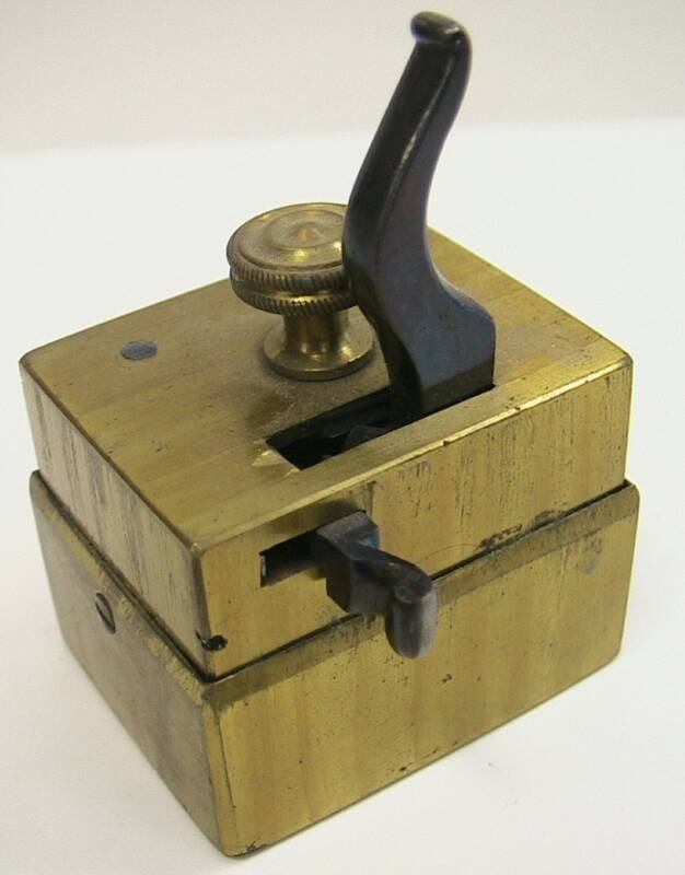 Unusual rectangular scarificator.  This piece is odd in the fusion of the later style box design and the earlier bar release mechanism.